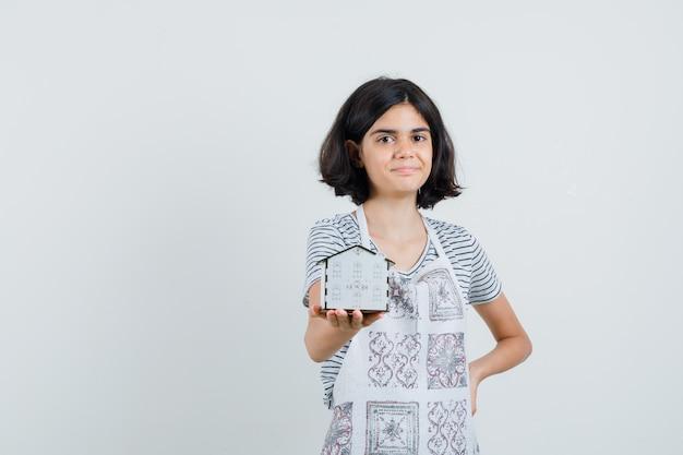 Meisje dat huismodel in t-shirt, schort voorstelt en vrolijk kijkt.