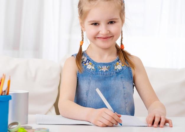 Meisje dat huiswerk doet bij bureau