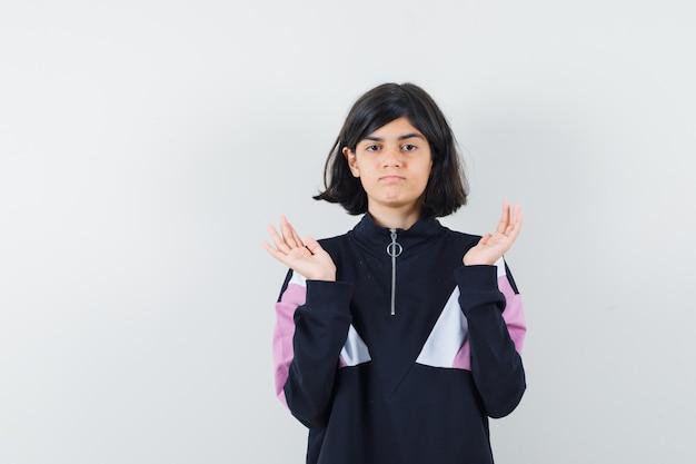 Meisje dat hulpeloos gebaar in overhemd toont en boos, vooraanzicht kijkt.