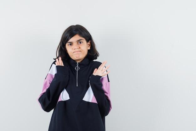 Meisje dat hulpeloos gebaar in overhemd toont en verward kijkt. vooraanzicht.