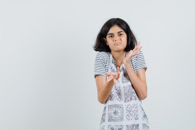 Meisje dat hulpeloos gebaar in t-shirt, schort toont en verward kijkt