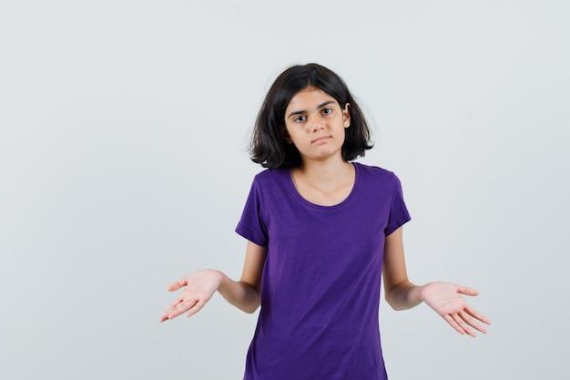 Meisje dat hulpeloos gebaar in t-shirt toont en verward kijkt