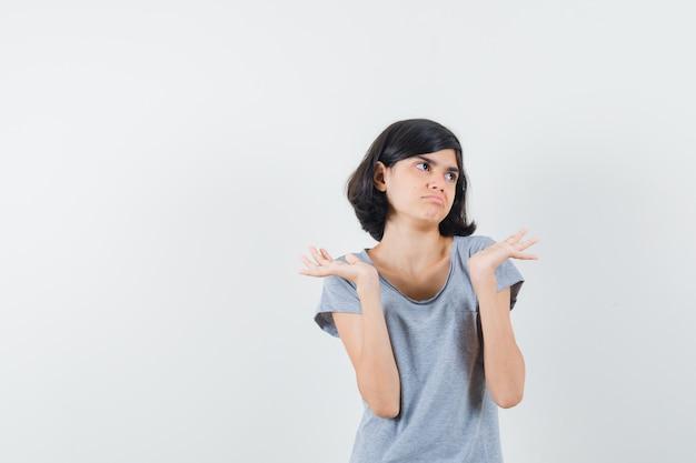 Meisje dat hulpeloos gebaar in t-shirt toont en verward, vooraanzicht kijkt.