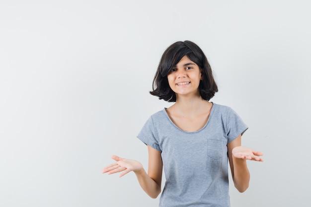 Meisje dat hulpeloos gebaar in t-shirt toont en vrolijk, vooraanzicht kijkt.