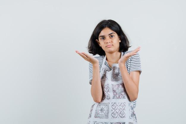 Meisje dat hulpeloos gebaar in t-shirt toont