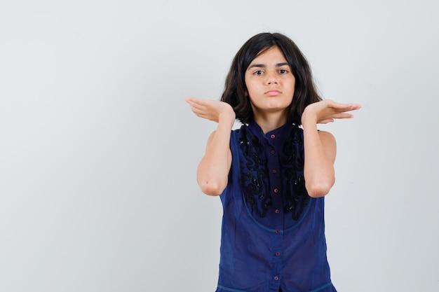 Meisje dat iets in blauwe blouse beweert vast te houden of op te heffen
