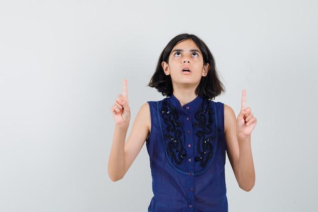 Meisje dat in blauwe blouse benadrukt en gericht kijkt.