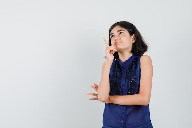 Meisje dat in blauwe blouse benadrukt en nieuwsgierig kijkt.