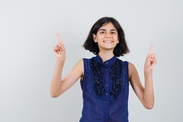 Meisje dat in blauwe blouse benadrukt en vrolijk kijkt