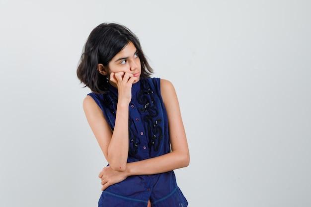 Meisje dat in blauwe blouse opzij kijkt in het denken stelt en nieuwsgierig kijkt.