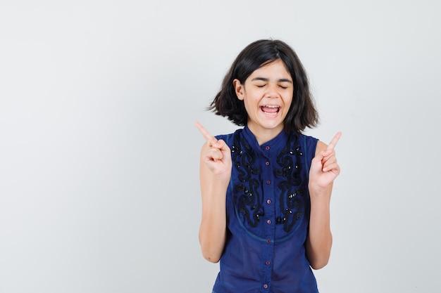 Meisje dat in blauwe blouse vingers benadrukt en zalig kijkt