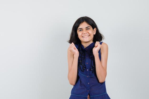 Meisje dat in blauwe blouse winnaargebaar toont en blij kijkt