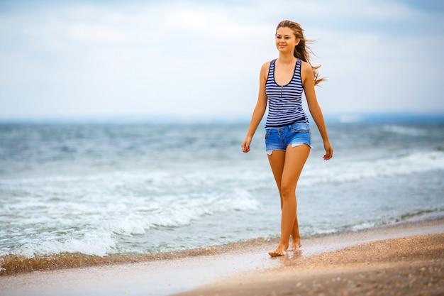 Meisje dat in borrels op het strand loopt