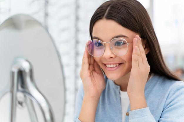 Meisje dat in de winkel een bril probeert