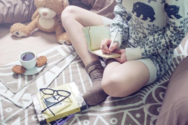 Meisje dat in een notitieboekjezitting schrijft op het bed