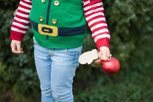 Meisje dat in elftrui en hoed op kerstmis in het hout wacht. halve lengte portret van een klein kind in de buurt van de kerstboom