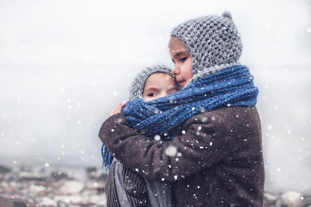 Meisje dat in gebreide grijze hoed haar bevroren kleinere broer koestert