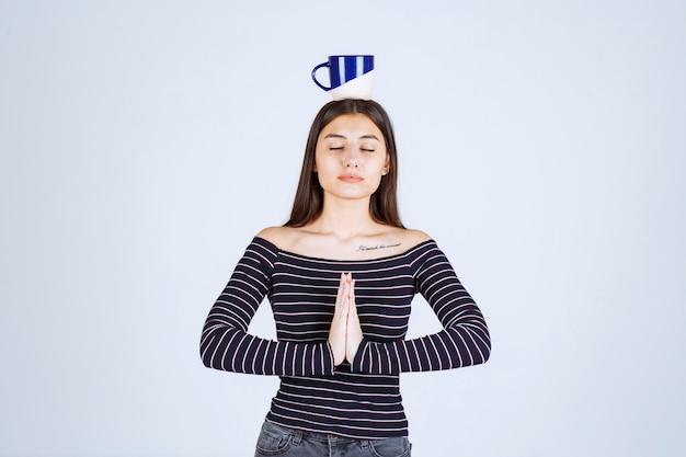Meisje dat in gestreept overhemd de koffiemok tegen haar hoofd zet.