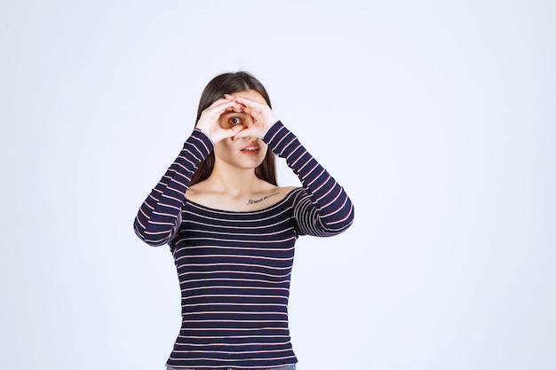 Meisje dat in gestreept overhemd door haar vingers kijkt.