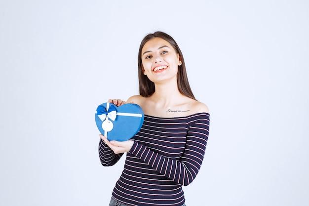 Meisje dat in gestreept overhemd een blauwe hartvormige giftdoos houdt en glimlacht.