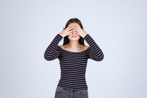 Meisje dat in gestreept overhemd haar hoofd houdt aangezien zij uitgeput is of hoofdpijn heeft.