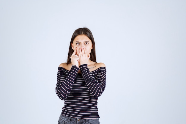 Meisje dat in gestreept overhemd luistert of roddelt.