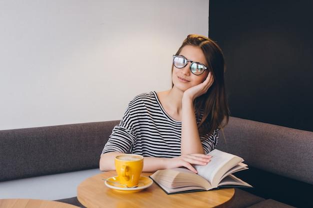 Meisje dat in glazen een boek in een koffiewinkel leest