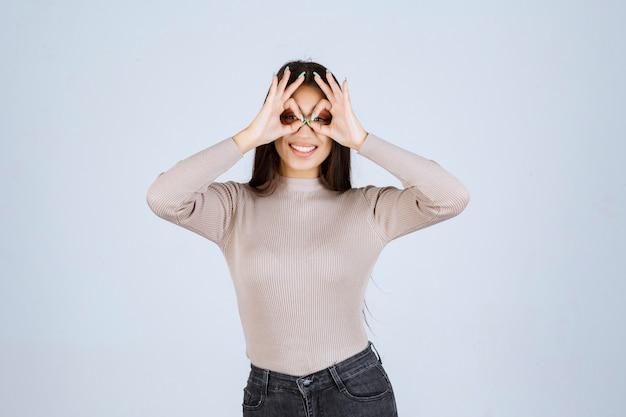 Meisje dat in grijs overhemd door vingers kijkt.