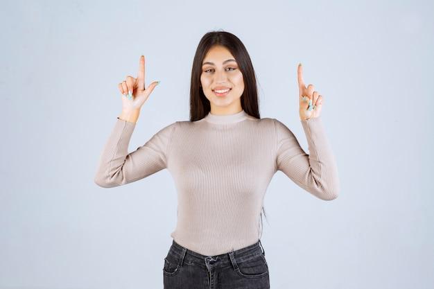 Meisje dat in grijze sweater iets hierboven richt.