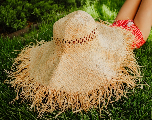 Meisje dat in grote strohoed op gras legt