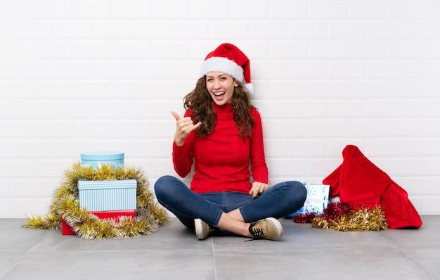 Meisje dat in kerstmisvakantie op de vloer zit die telefoongebaar maakt