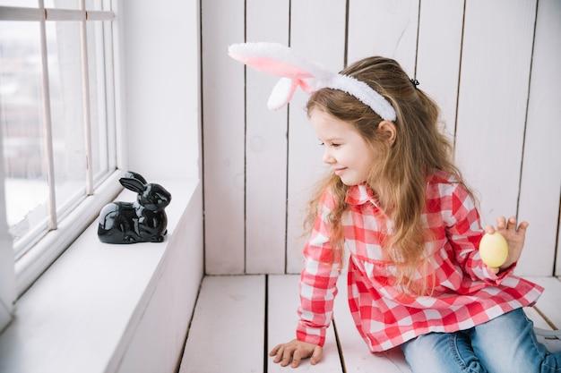 Meisje dat in konijntjesoren geel paasei houdt