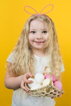 Meisje dat in konijntjesoren mand met paaseieren houdt