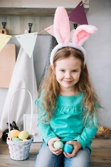 Meisje dat in konijntjesoren met mand van paaseieren zit