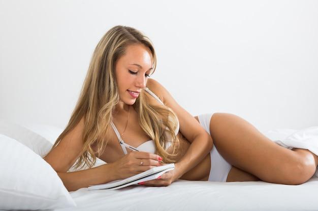 Meisje dat in notitieboekje in bed schrijft