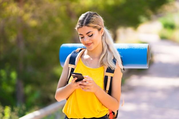 Meisje dat in openlucht wandelt die een bericht met mobiel verzendt