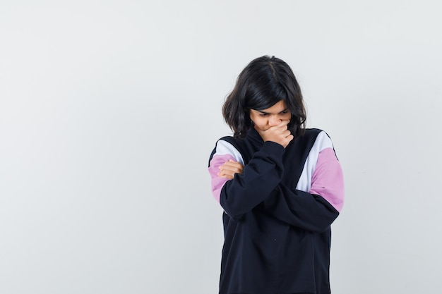 Meisje dat in overhemd haar kin houdt terwijl naar beneden kijkt en peinzend, vooraanzicht kijkt.