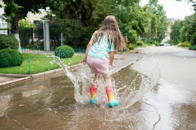 Meisje dat in regenboogrubberlaarzen in plassen dichtbij het huis springt