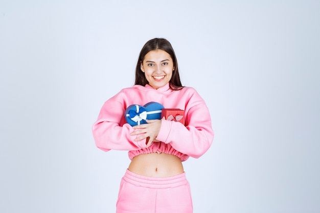 Meisje dat in roze pyjama de rode en blauwe giftdozen van de hartvorm koestert.