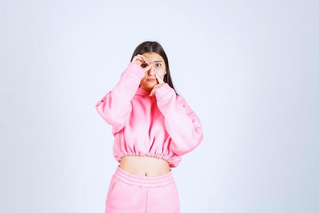 Meisje dat in roze pyjama's door haar vingers kijkt