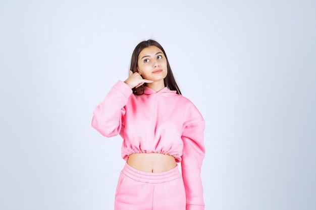 Meisje dat in roze pyjama's vraagt om te bellen