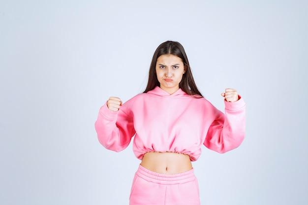 Meisje dat in roze pyjama zeer agressief en boos gezicht maakt
