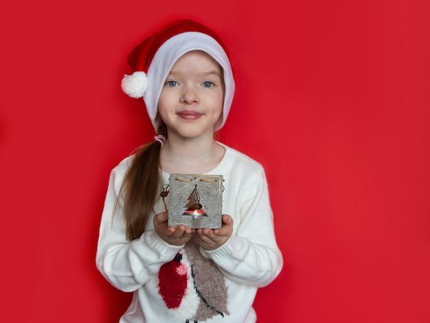 Meisje dat in santahoed de kandelaar van kerstmis houdt