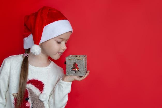 Meisje dat in santahoed een concept van het kandelaarnieuwjaar en kerstmis houdt