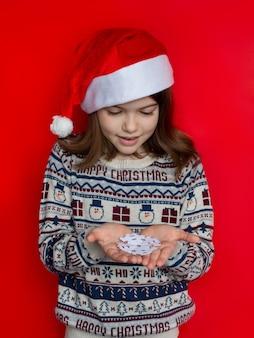 Meisje dat in santahoed een sneeuwvlok nieuw jaar en kerstmisconcept houdt