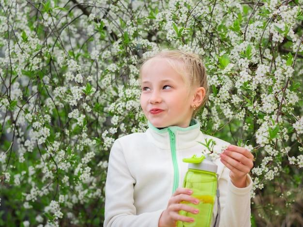 Meisje dat in sportenkleren een fles verfrissende drank in kersenbloesems houdt