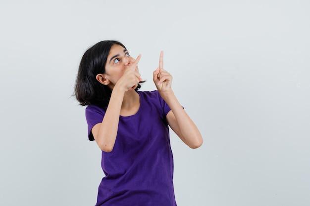 Meisje dat in t-shirt benadrukt en verbaasd kijkt