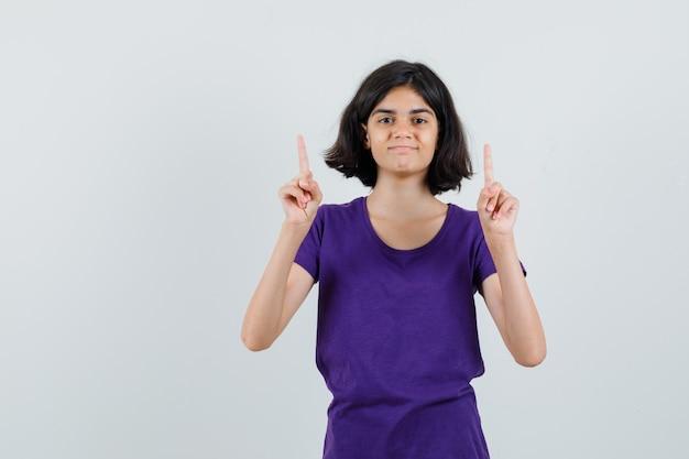 Meisje dat in t-shirt benadrukt en zelfverzekerd kijkt.