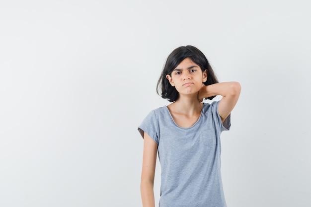Meisje dat in t-shirt hand op hals houdt en peinzend, vooraanzicht kijkt.