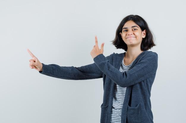 Meisje dat in t-shirt, jasje benadrukt en vrolijk kijkt